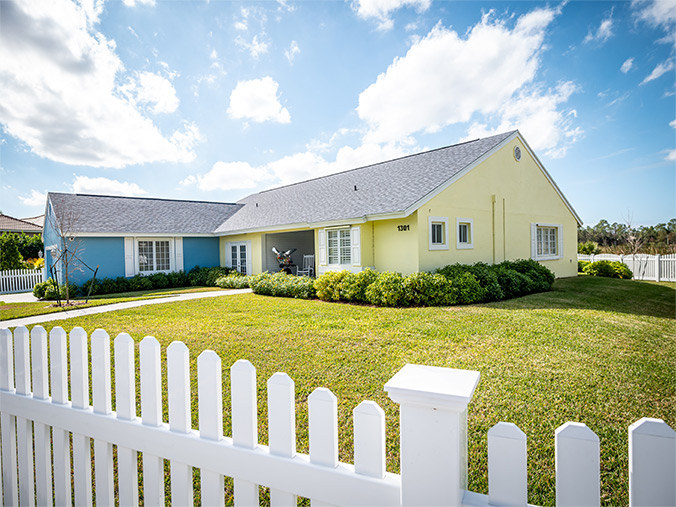 A blue and yellow house with a white picket fence