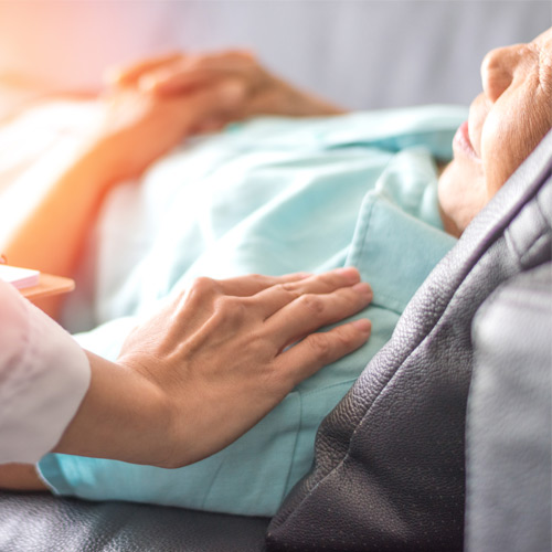 A nurse places a hand on an elderly patient