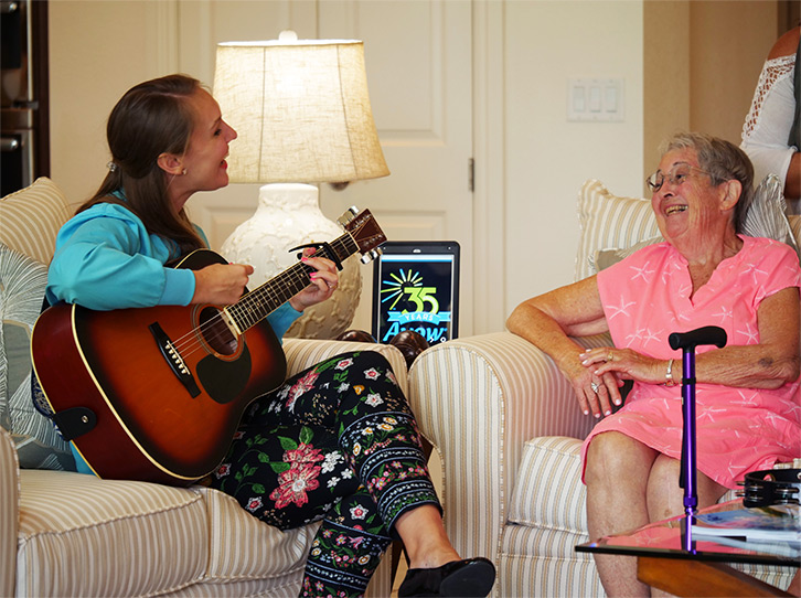 A woman plays guitar for a patient