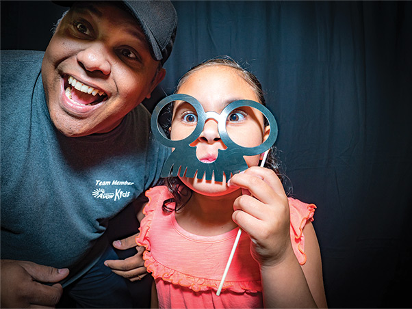 A kid and an adult playing with photo booth props