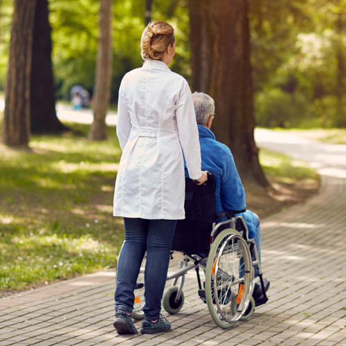 A nurse pushes a man in a wheelchair